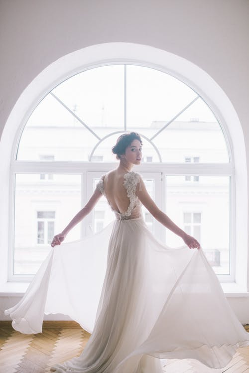 Back view of young slim lady in elegant dress demonstrating wedding dress with bare back near big window with arch in spacious room