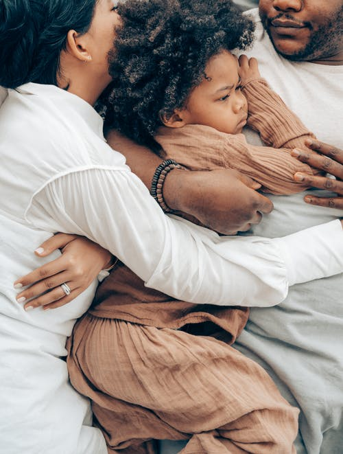 Top view of charming African American child and parents in pajamas lying together hugging each other on bed