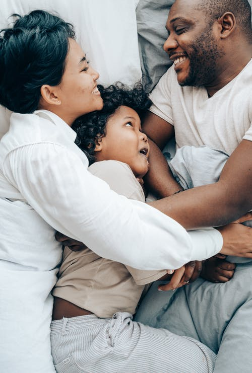 Happy ethnic family hugging each other in bed