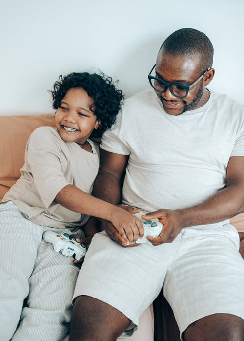 From above of positive African American child using gamepad with father while playing game console resting together in cozy living room