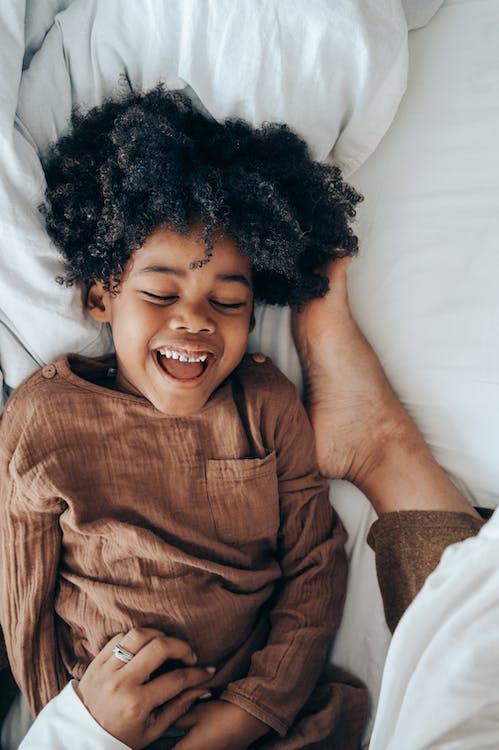 Happy African American boy lying on bed near legs of mom
