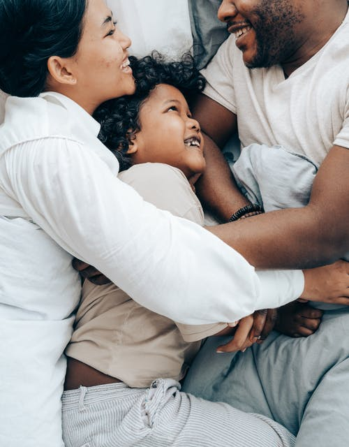 Happy ethnic mother and kid hugging father in bed