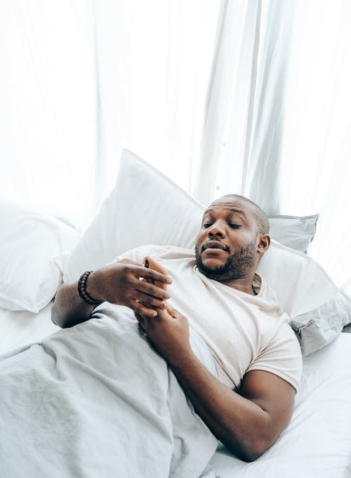 Adult black man using smartphone in bed