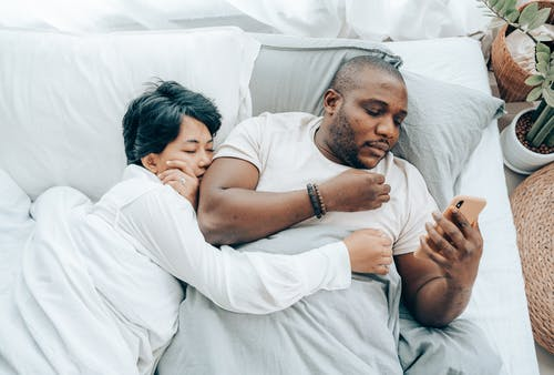 African American man using smartphone in bed near sleeping wife