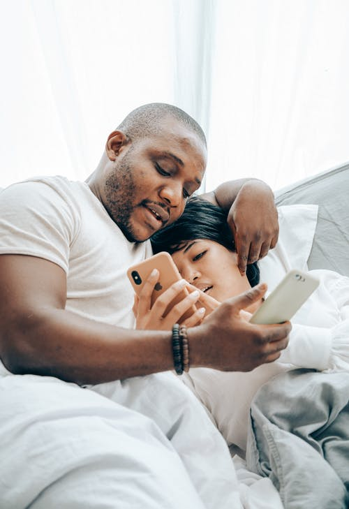 Cheerful young spouses messaging on smartphones in bed