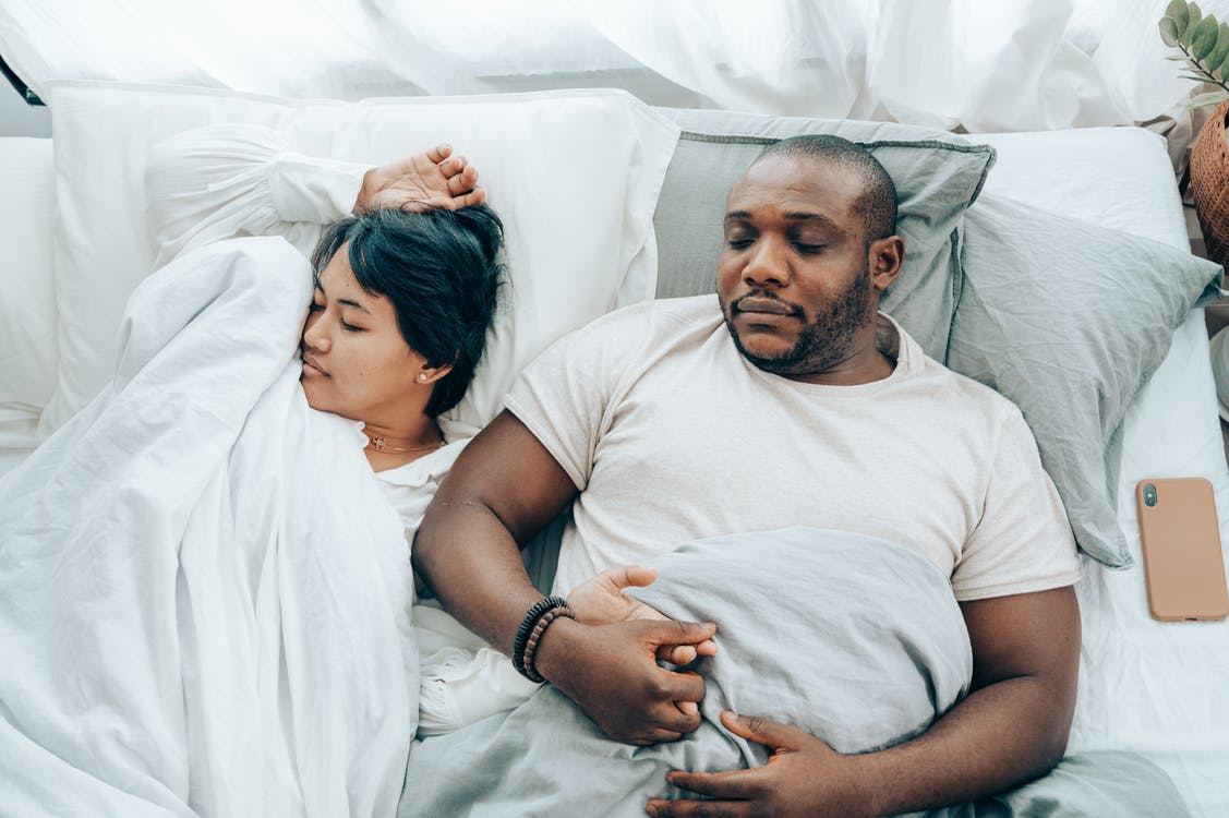 Young multiethnic spouses sleeping in bed holding hands