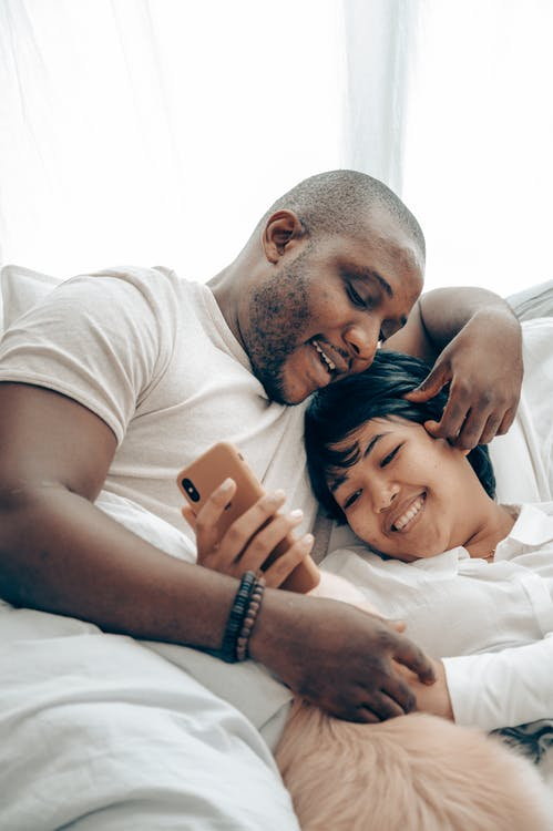 Cheerful young diverse couple lying together in bed and smiling while watching video on mobile phone in morning