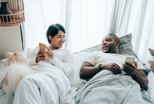 Positive young multiethnic spouses communicating while lying in bed