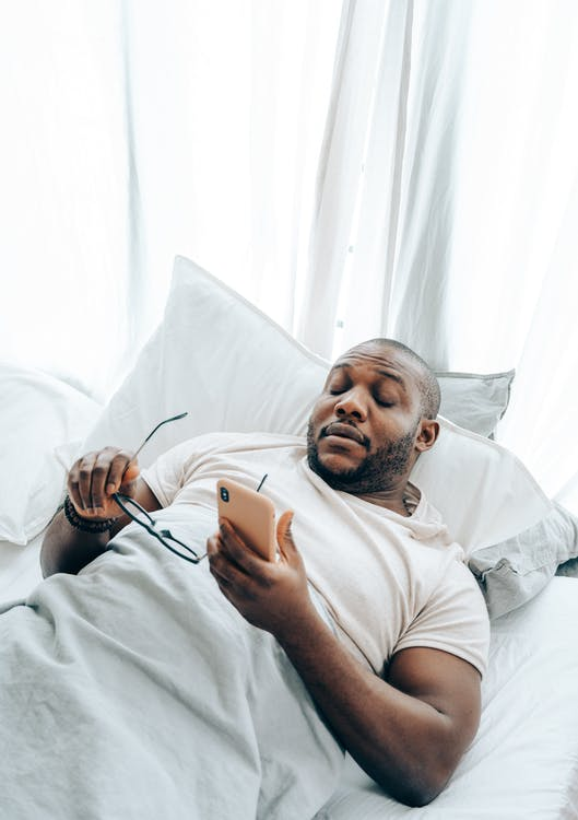 From above of young African American male getting phone call while lying and sleeping in bed