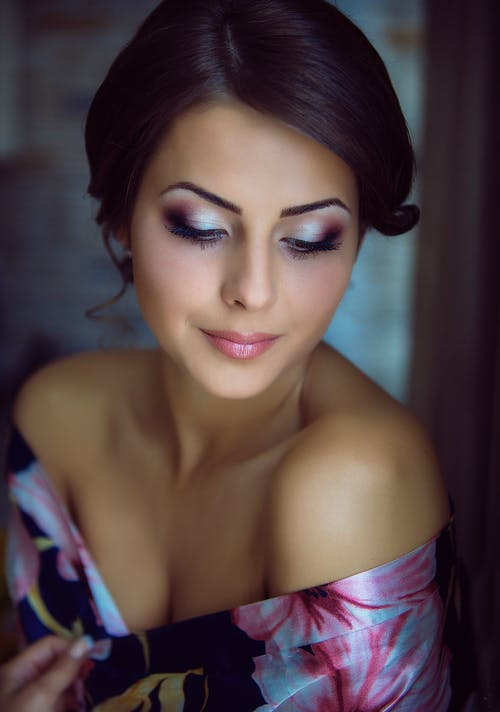 Crop charming feminine woman with bright makeup at home