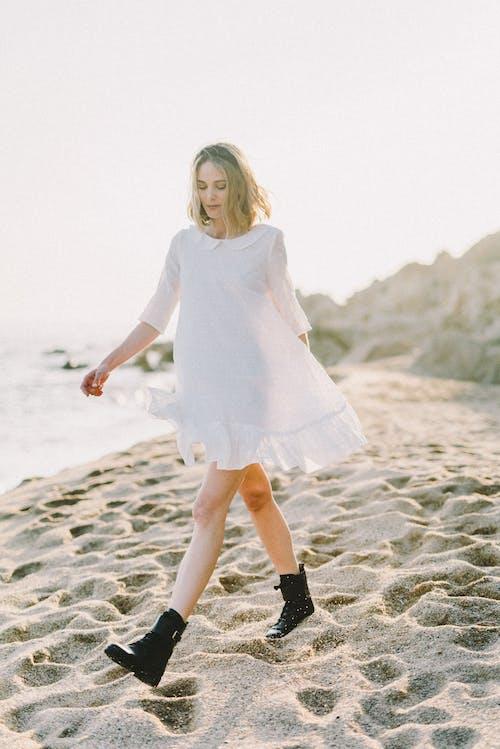 Mädchen Im Weißen Langarmkleid, Das Auf Weißem Sand Steht
