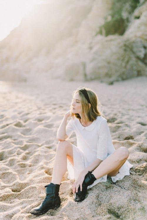 Frau Im Weißen Langarmhemd, Das Auf Weißem Sand Sitzt