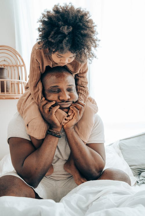 Black father and kid having fun in bedroom