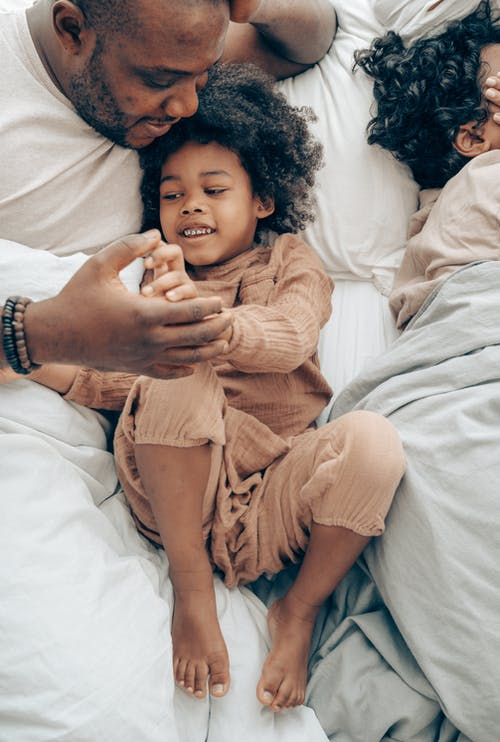 Ethnic man playing with kid in bedroom
