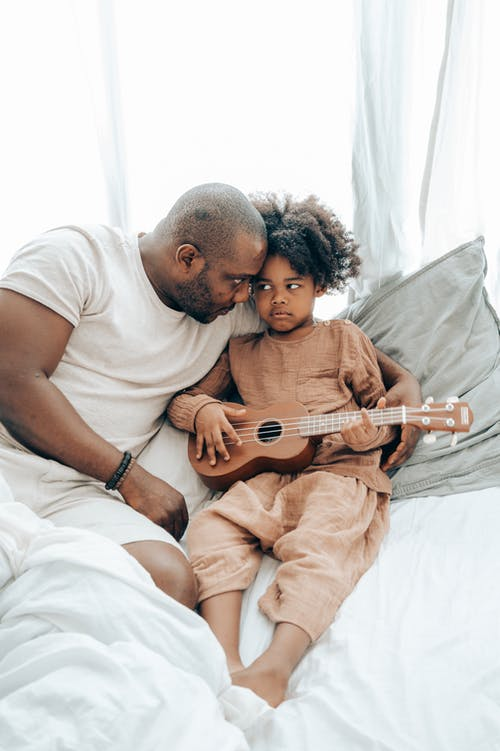 Ethnic kid with guitar and father on bed at home