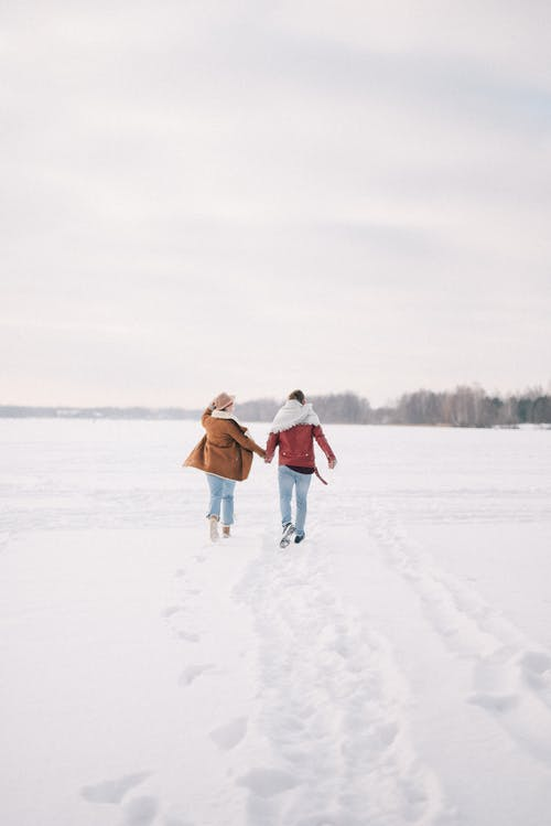 People Walking on Snow Covered Field Holding Hands