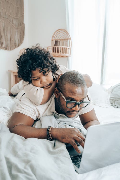 Black father and kid browsing laptop together in bedroom