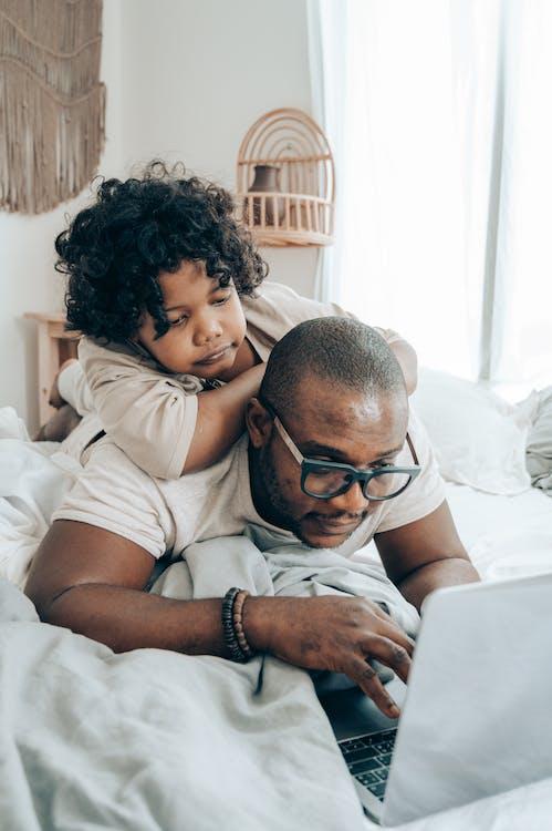 Black man and kid browsing laptop in bedroom