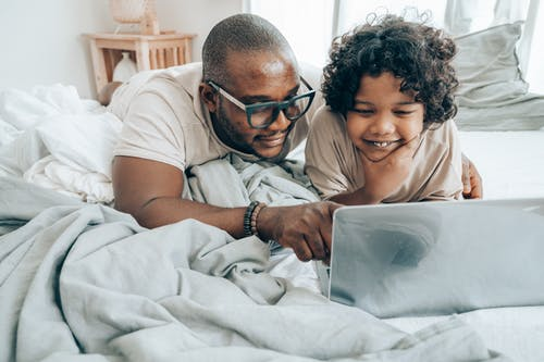 Happy father and child browsing laptop in bedroom