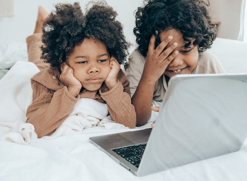 Sad black boy using laptop with smiley brother