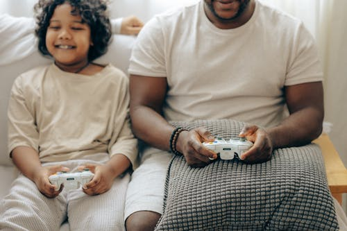 Crop smiling black father and son in sleepwear playing with joysticks on game console together while sitting on sofa in light living room