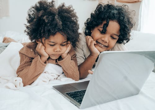 Ethnic little brothers using laptop on bed