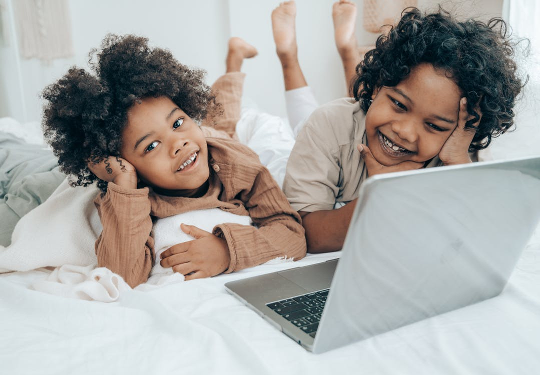 Smiley black boys watching funny video on laptop on bed