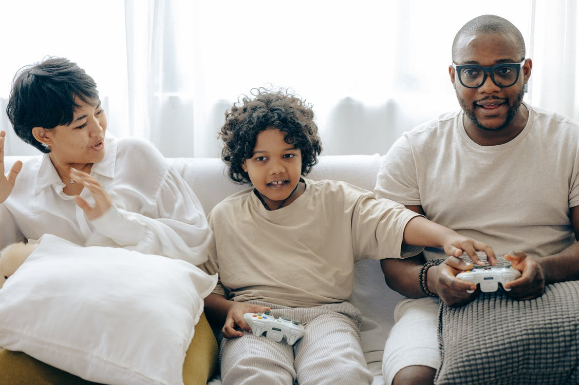 Interested ethnic kid preventing father from winning in video game while resting together with mother in living room