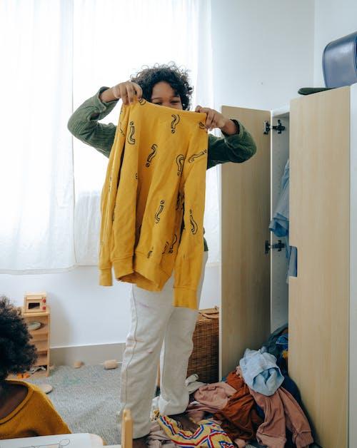 Black teenager choosing clothes in bedroom