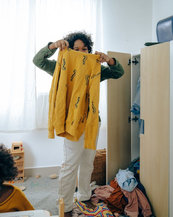 Unrecognizable African American teen girl in casual wear holding yellow sweater while sorting clothes in wardrobe in room