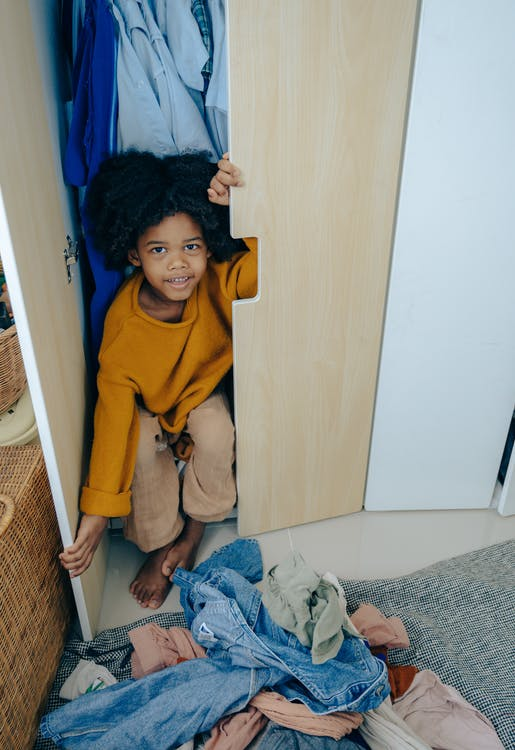 Playful little African American kid sitting in wardrobe in bedroom
