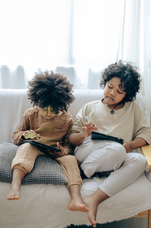 Little black kids using tablets on couch at home