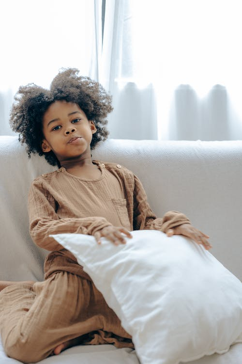 Mischievous little black girl resting on sofa with pillow