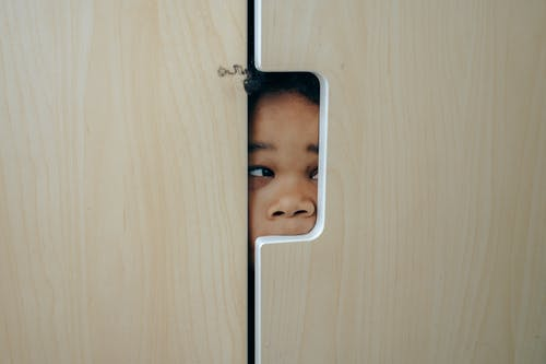 Anonymous funny little ethnic child hiding in wardrobe and peeping through hole while playing at home