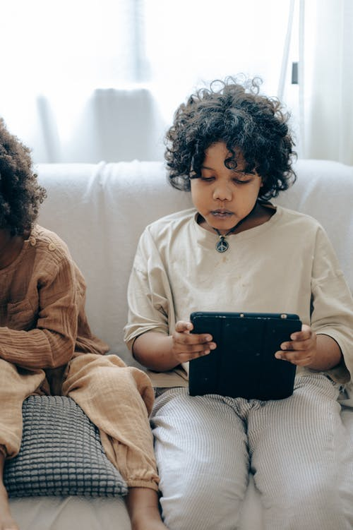 Concentrated black kid using tablet on couch