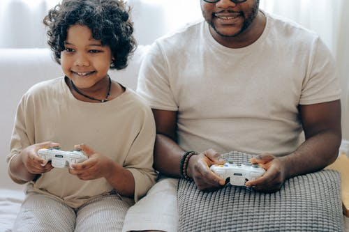 Positive black little girl playing video game with father