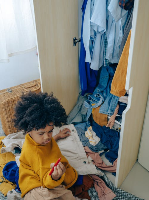 Curious little black kid making mess of clothes in wardrobe