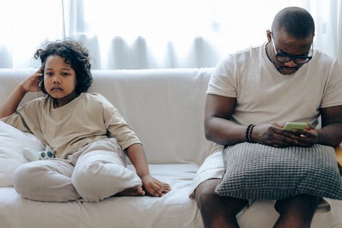 Young African American man surfing internet on mobile phone sitting on sofa together with daughter watching TV