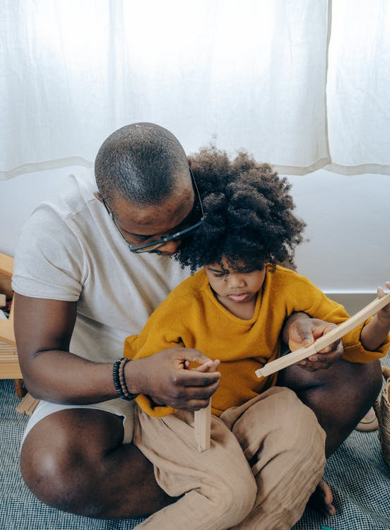 High angle of young black man taking care of little daughter while playing together sitting on floor