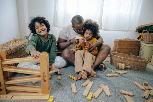 Cute black girls collecting wooden details of constructor with father while spending weekend together at home