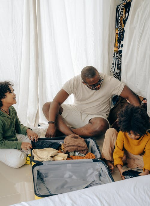 From above of young African American man sitting on floor and packing suitcase with little daughters