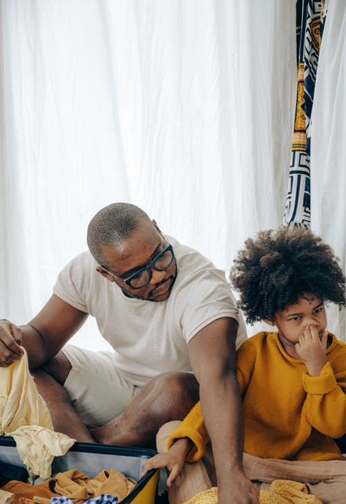 Funny little black girl picking nose sitting near concentrated father packing suitcase for holidays