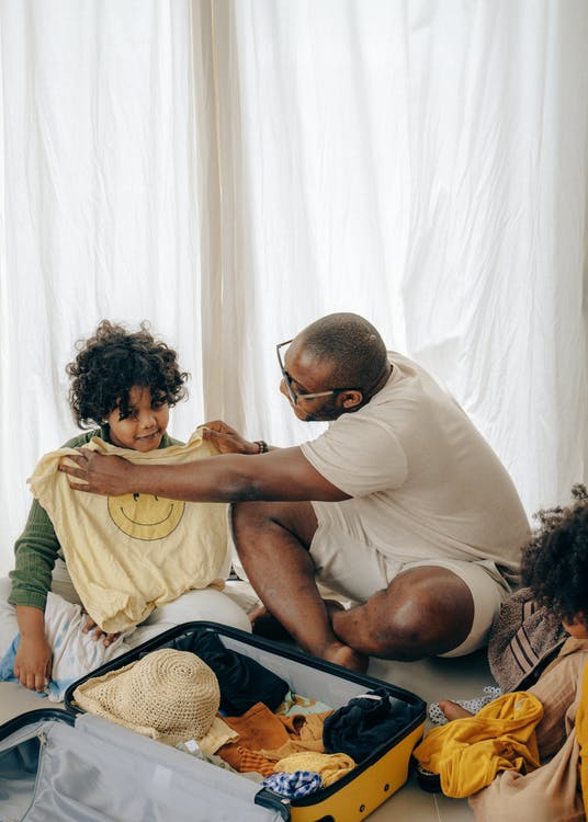 Black dad and kid sorting clothes while packing suitcase