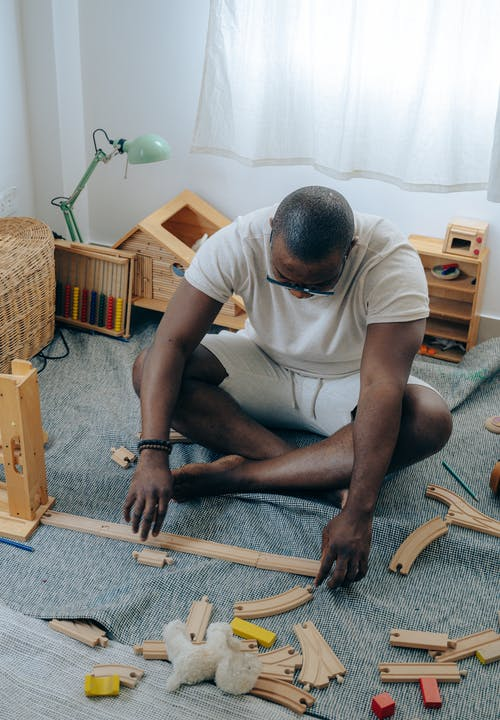African American man sitting on floor near wooden details
