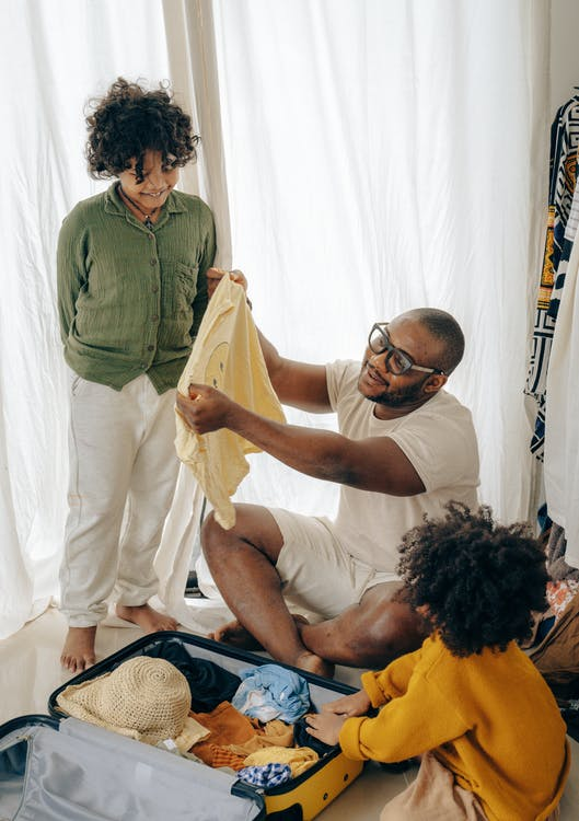 Content black father with kids packing suitcase