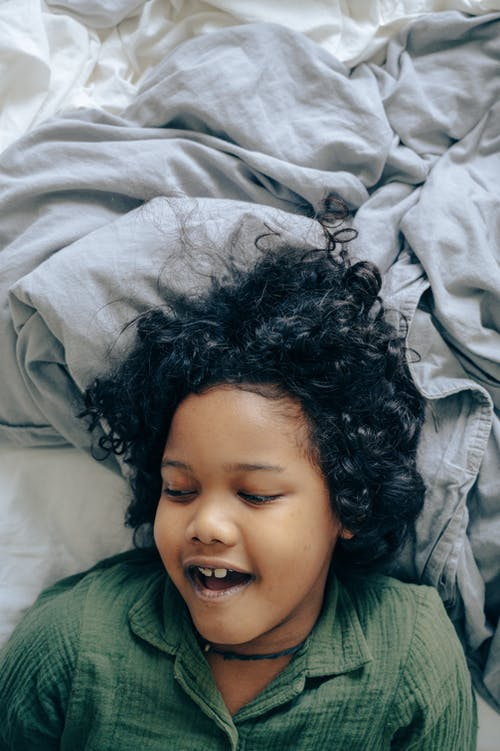 Happy black child lying on bed