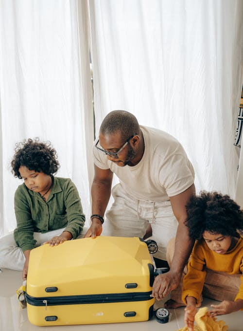 Black father and children packing luggage