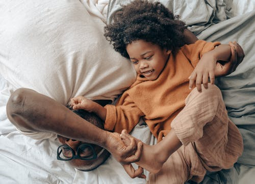 Black father and kid lying on bed