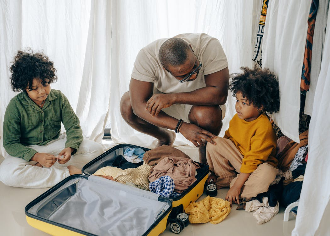 African American father in eyewear with sad kids with curly hair sitting near opened suitcase