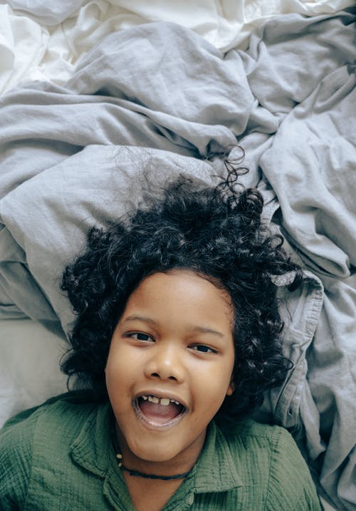 Cheerful black child lying on bed